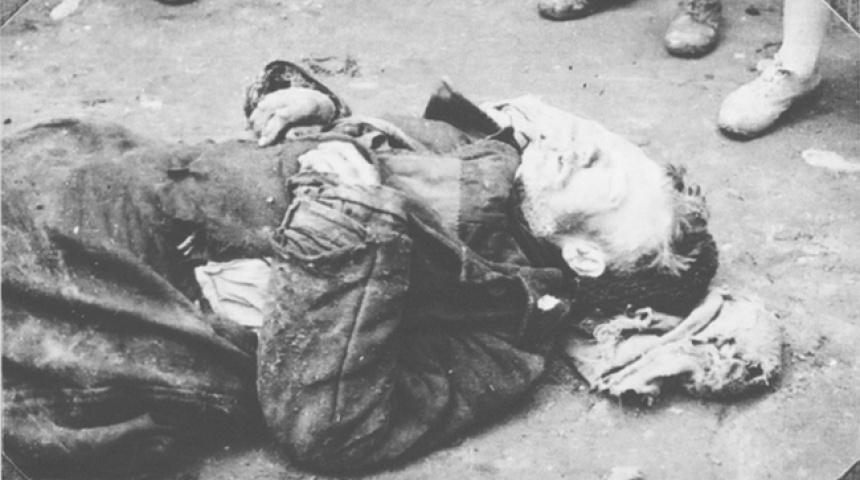 Чорно-біле фото чоловіка, що лежить горілиць на вулиці