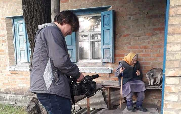 Оператор Олексій Жиленко знімає на відео літню жінку, свідка Голодомору, на фоні її будинку.