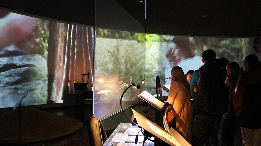 Посетители музея рассматривают Книги памяти и смотрят фильм, транслируемый на стене