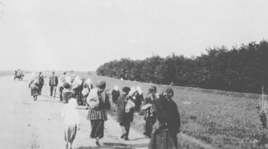 Чорно-біле фото, дорогою йдуть люди з торбинками на плечах