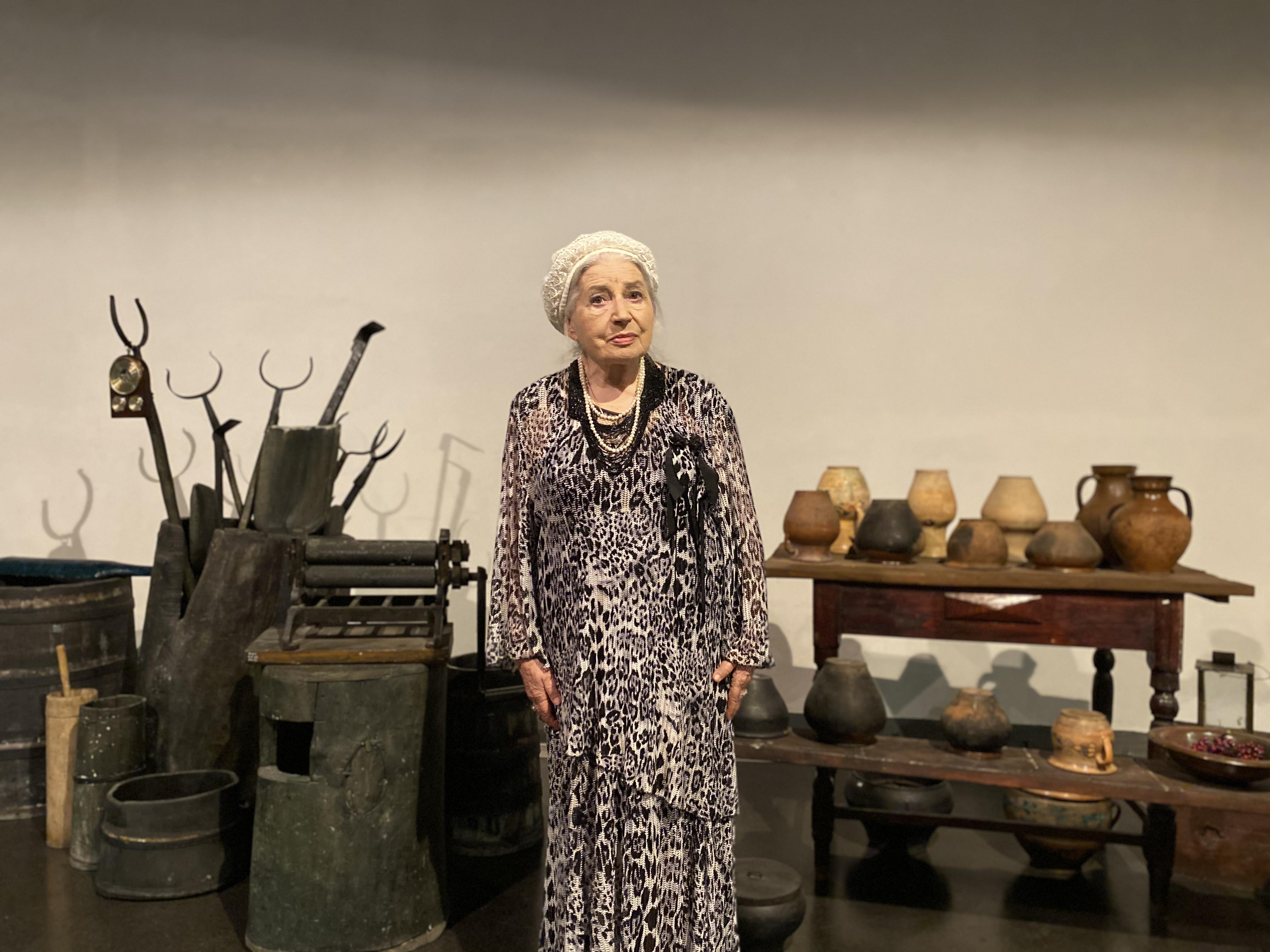 На фото - Галина Яблонська, літня жінка у білому береті та чорно-білій леопардовій сукні на фоні музейної експозиції