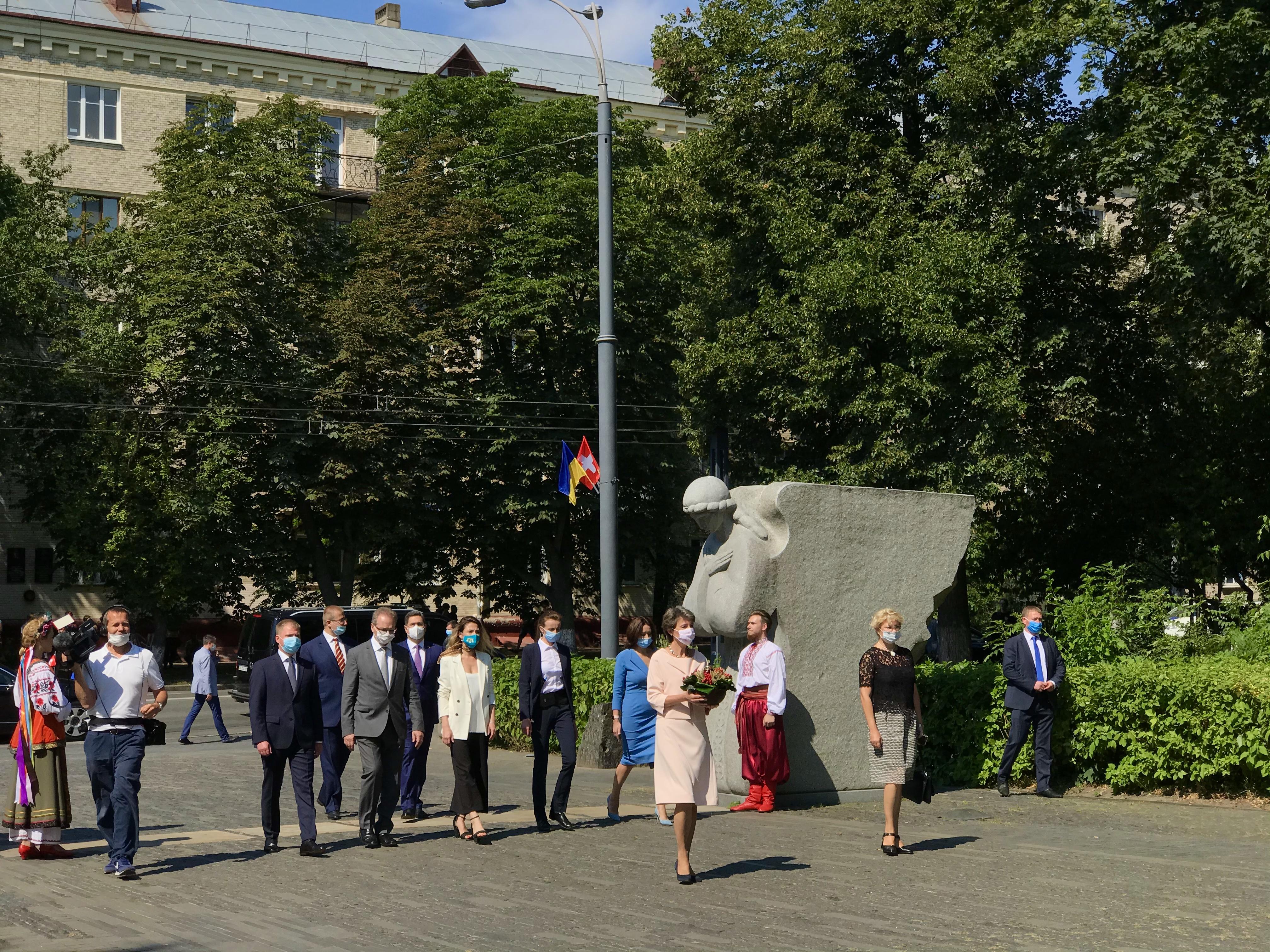 На фото Президент Швейцарської конфедерації разом з супроводом на фоні фрагмента скульптурної композиції Янголи скорботи, які розташовані біля входу на територію музею