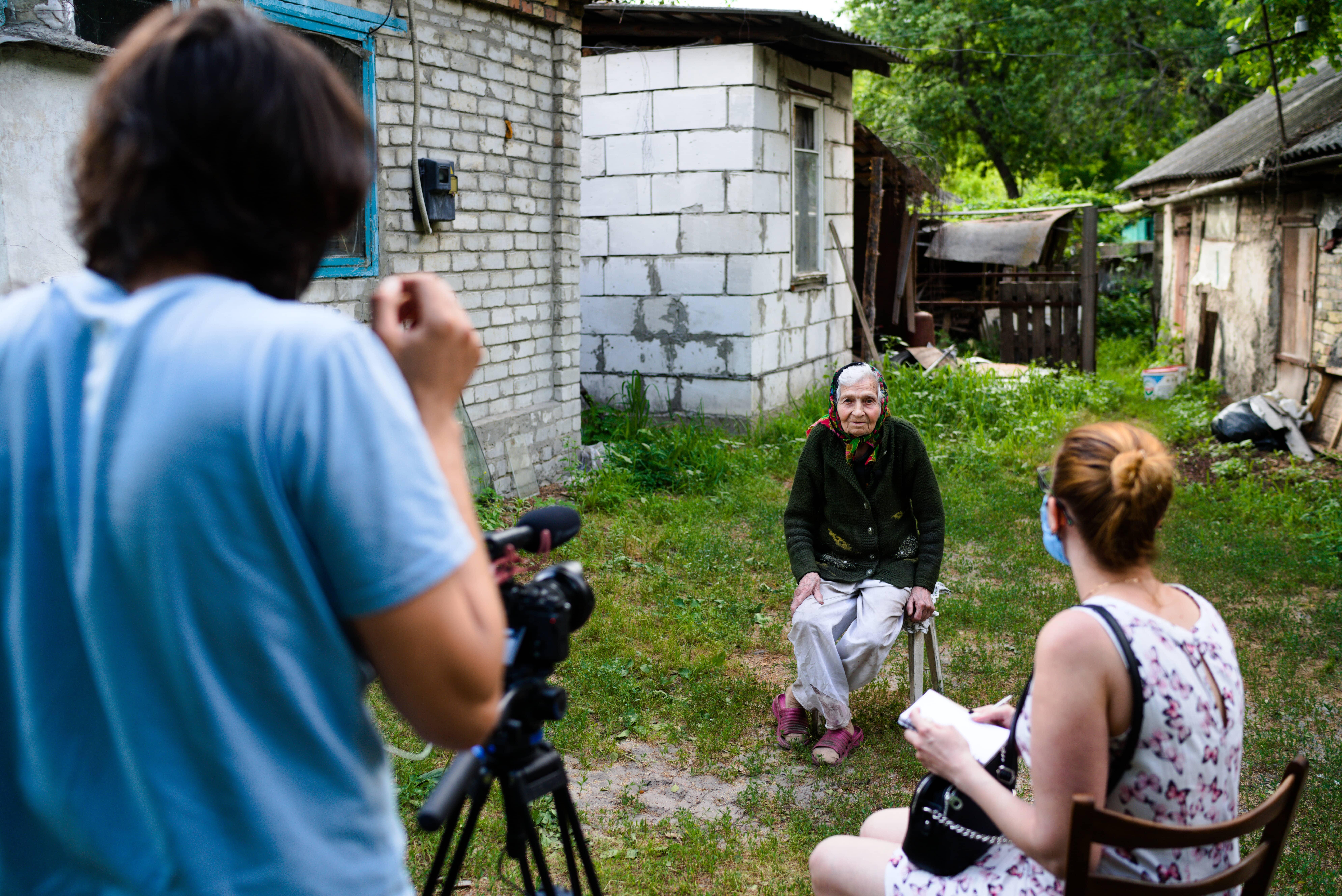 На фото посеред двору на табуреті обличчям до глядача сидить літня жінка-свідок Голодомору, спиною до глядача оператор з камерою та співробітниця музею Лариса Артеменко, що проводить опитування