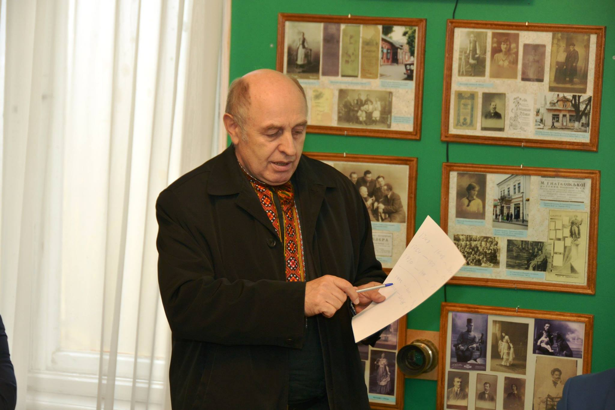 На фото - професор Сергійчук читає доповідь на фоні стендів з фотографіями. Він одягнений у темний піджак та вишиту червоними нитками сорочку