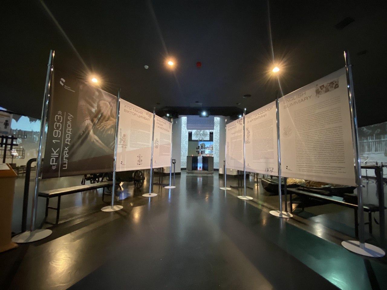 На фото - вигляд виставки від входу до Зали пам'яті. Це прохід до центральної частини зали, зліва та справа розташовані по три банера з зображенням картини та описом виставки