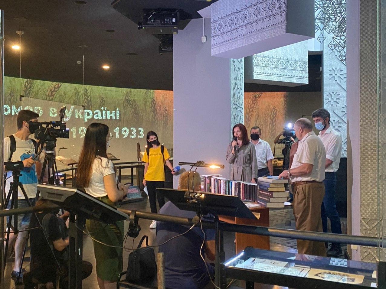 На фото зображені люди, які стоять у центрі зали пам'яті Музею Голодомору. Людей знімають ЗМІ, які завітали до