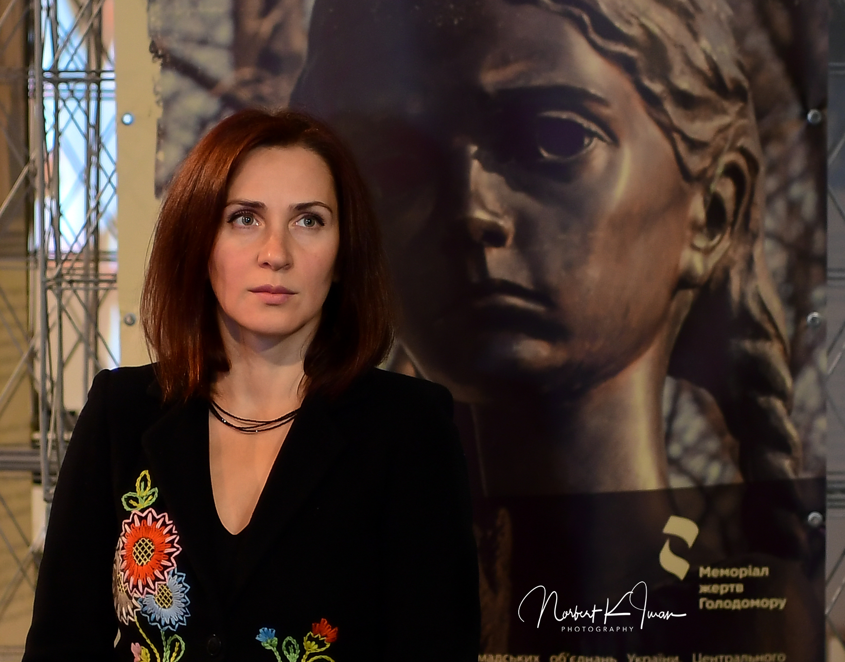 На фото зображена Олеся Стасюк у чорному піджаку, що прикрашають вишиті кольорові квіти, на фоні фотографії обличчя скульптури дівчинки з 5 колосками