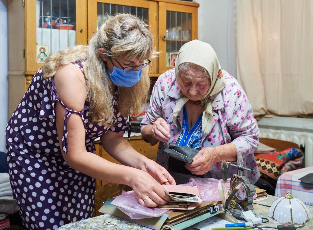 Співробітниця музею Юлія Коцур разом з літньою жінкою-свідком Голодомору переглядають сімейний фотоархів