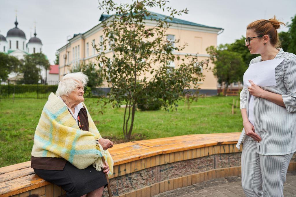 Співробітниця Музею Голодомору, тримаючи в руках опитувальник, розмовляє зі свідком Голодомору, літньою жінкою. Остання сидить на лавці у парку, а співробітниця музею стоїть справа обличчям до неї.