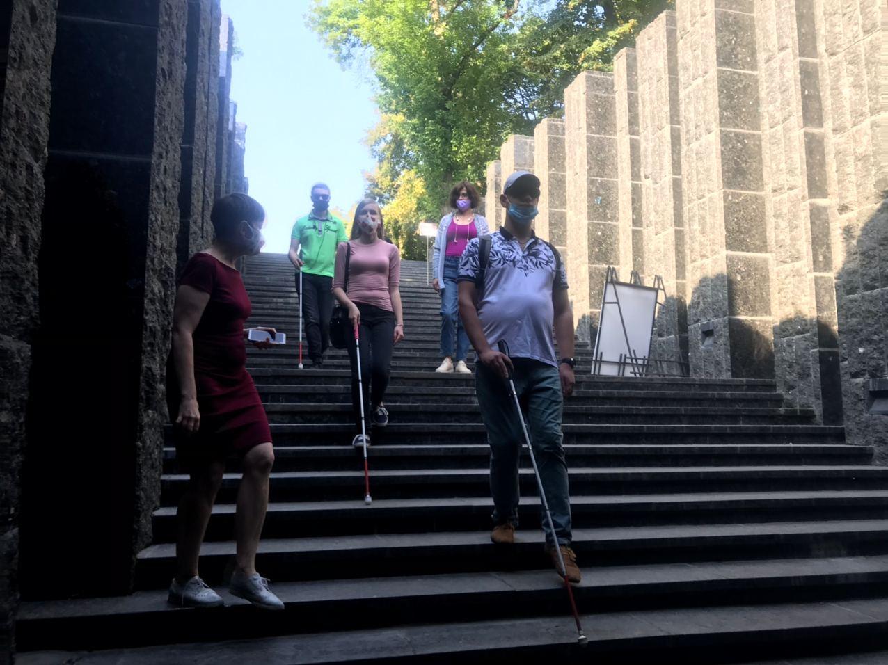 Незрячі відвідувачі спускаються сходами, використовуючи тростини